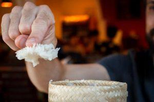 Porção de arroz glutinoso preso no dedo