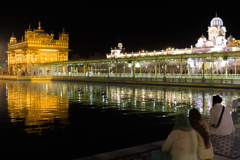 people looking at the golden temple lights during the night