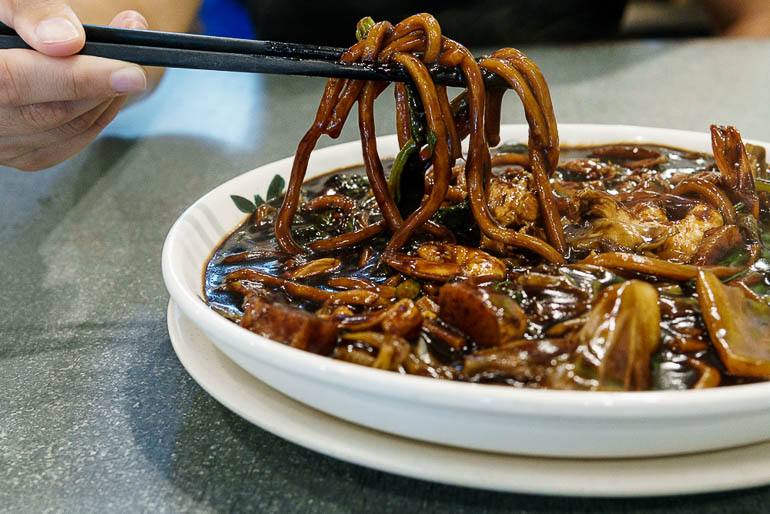 a plate with hokkien mee a typical malaysian dish