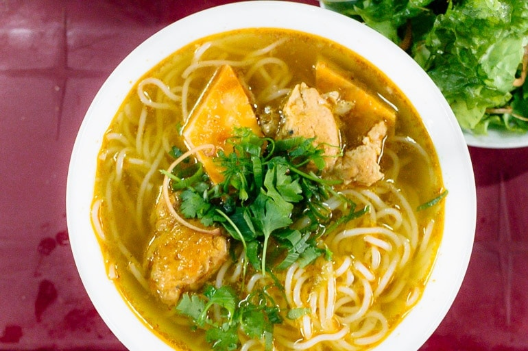 Bun Bo Hue bowl with rice noodle, beef, and the typical broth of this dish made with meat, bones, lemon grass, shrimp paste, and other local ingredients.