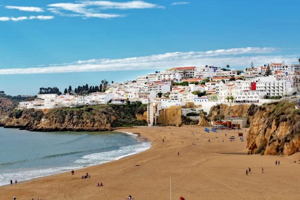 beach in albufeira in the algarve with the view of the hill and white houses