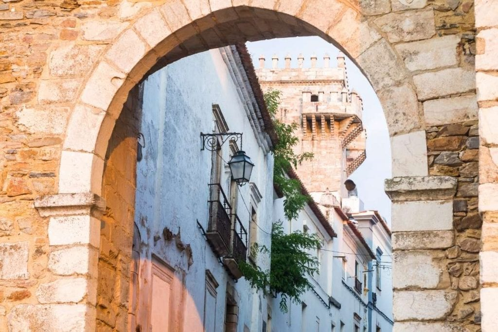 one of the entrance marble gates in Estremoz city with traditional white houses and a tower in the interior part located in central Alentejo and very popular place to visit in Portugal