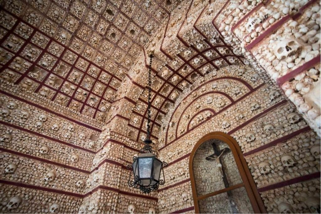 inside the bones chapel with walls decorated with skulls and bones in the city of Faro in Algarve