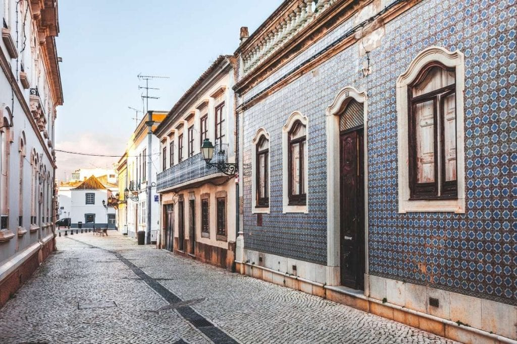 cobblestone street with traditional houses with tiles on their facades in the city of Faro in the Algarve