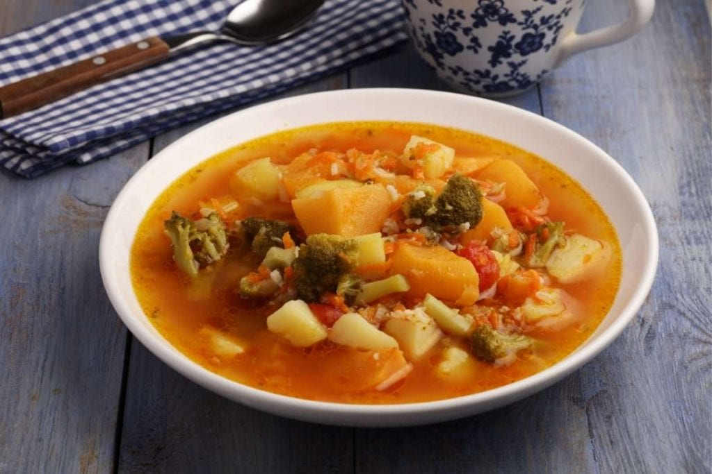 a small bowl with italian minestrone soup made with several vegetables