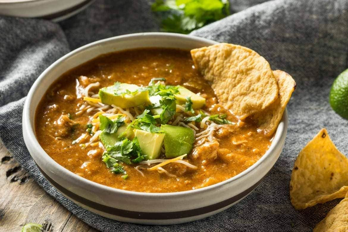a delicious bowl with tortilla soup typical of mexico with tortillas, avocado and coriander on top - one of the most famous soups in the world
