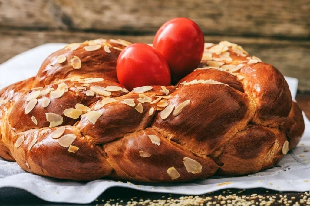 greek tsoureki braided bread with red painted eggs on top