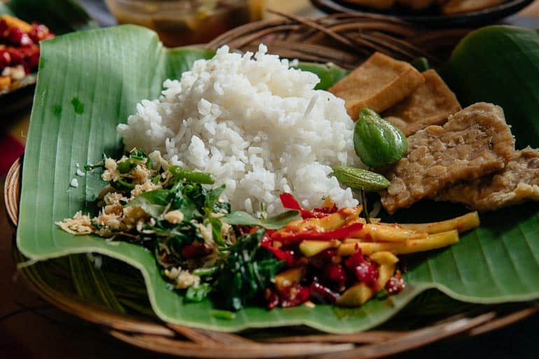 Indonesian dish server on a rattan plate covered by banana leaf
