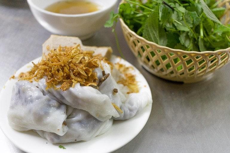 comida típica do norte do Vietnã do norte, feita com farinha de arroz cozida no vapor recheada com cogumelos, carne e servida com ervas frescas