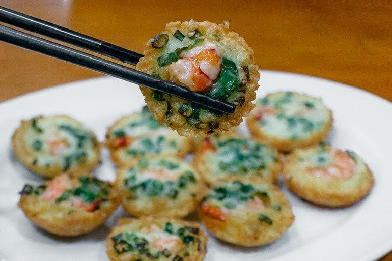 o Banh Kot são bolinhos feitos com farinha de arroz, amido de milho, cúrcuma e leite de coco com cobertura de camarão e cebolinha.