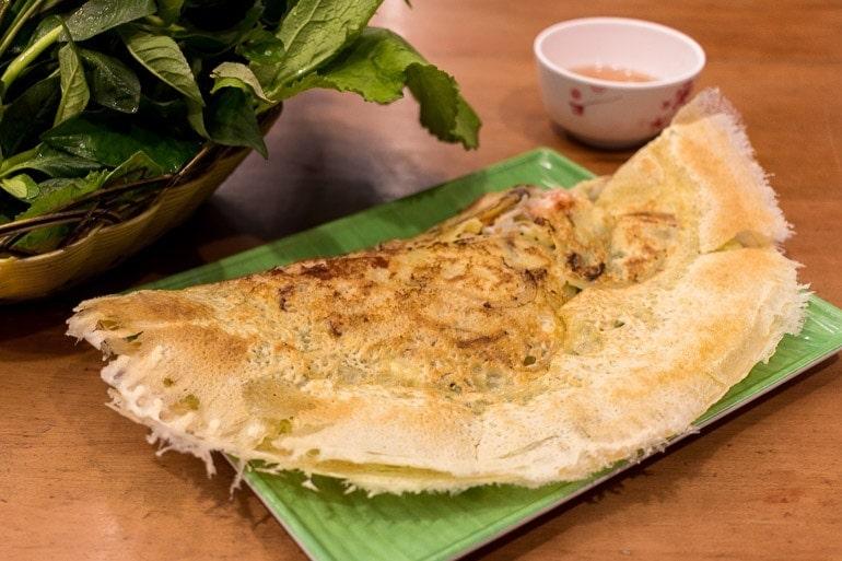 um dos pratos típicos do Vietnã, o Bahn xeo parece um crepe feito com farinha de arroz e cúrcuma recheado com carne de porco, camarão e broto de feijão