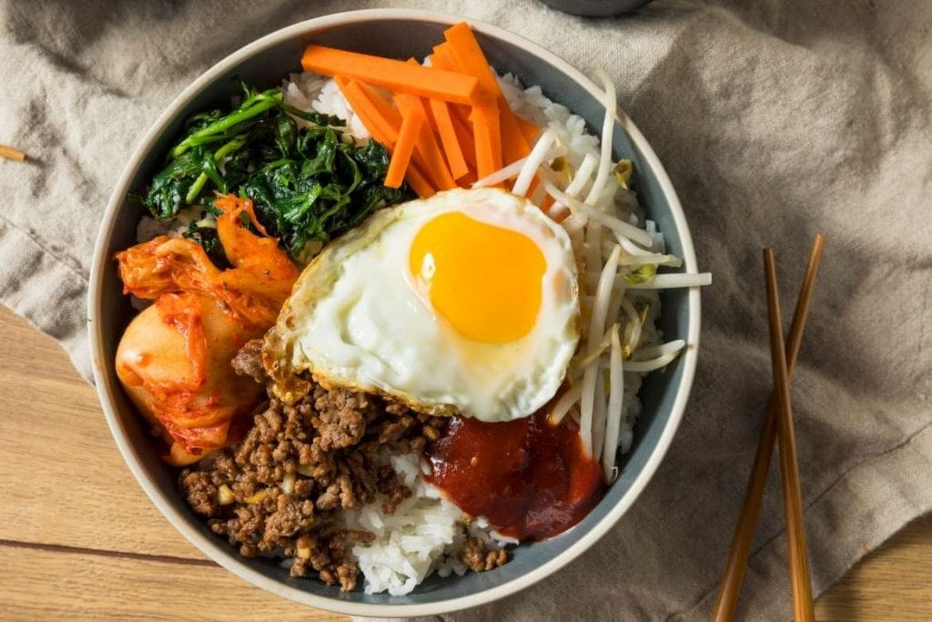 a bowl with bibimbap a famous korean rice dish with vegetables, egg, rice and other ingredients