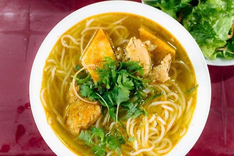 Bun Bo Hue bowl com noodle de arroz, carne, e o caldo típico deste prato feito com carne, ossos, capim limão, pasta de camarão, e outros ingredientes locais.