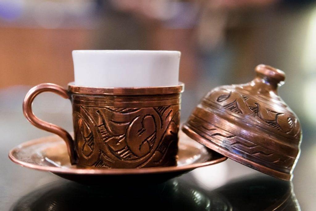 xícara tradicional de café turco em porcelana com um conjunto em cobre