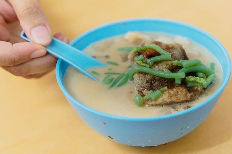 uma tigela azul com cendol and raspadinha de gelo sobremesa típica da Malásia