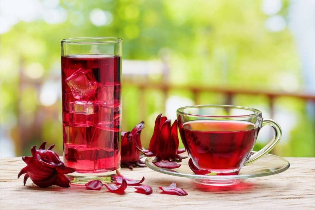 two cups with hibiscus infusion, one with ice cold hibiscus tea and another hot hibiscus tea