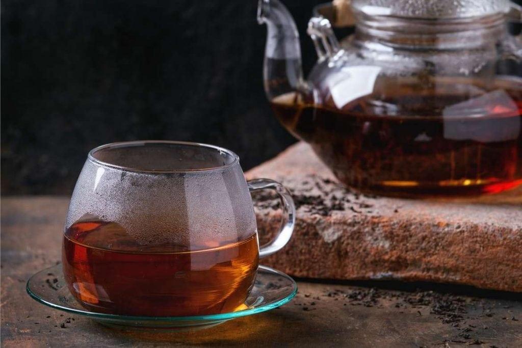 uma xícara translúcida com chá preto pronto para beber