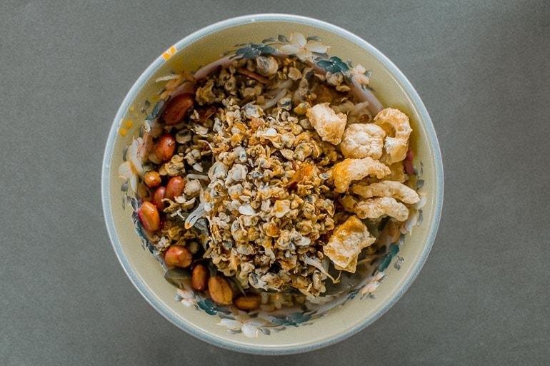 uma tigela de Com Hen, um dos pratos típicos do Vietnã da cidade de Hue feito com arroz de mariscos, amendoim, e pururuca de pele de porco