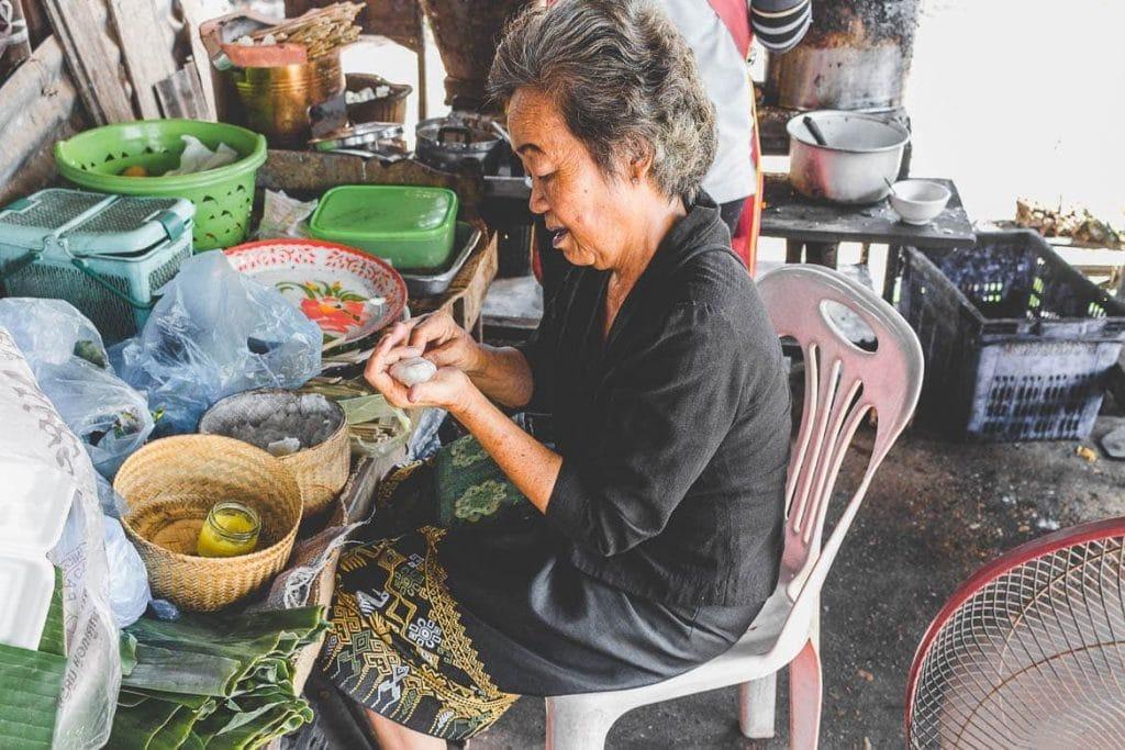 Senhora fazendo Khao Jee em restaurante local