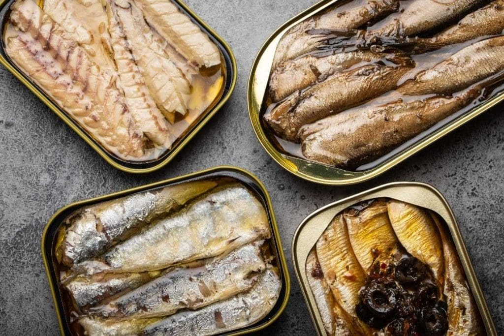 Four tin cans open with different types of canned fish