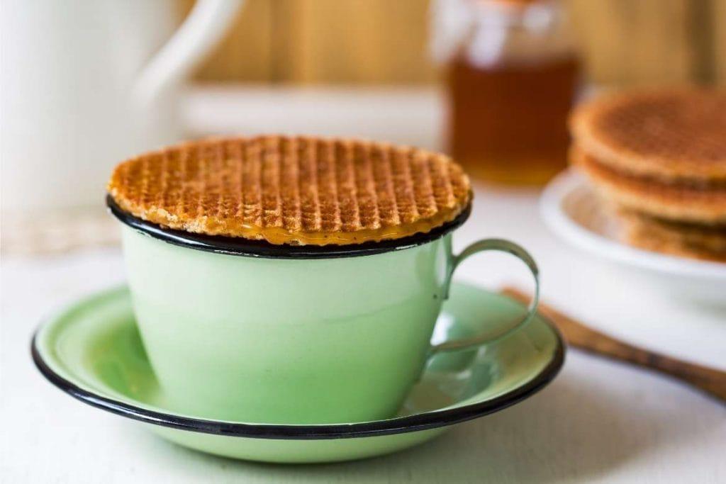 uma xícara com café holandês e stroopwafel em cima faz de Amsterdam um excelente destino para café