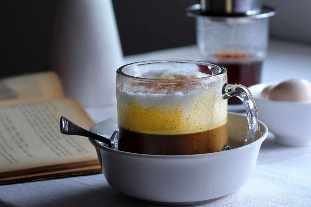café com ovo vietnamita com os ovos e café preto filtrado com um phin no fundo