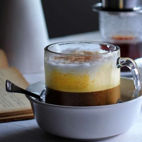 vietnamese egg coffee with eggs and black coffee filtered with a phin on the background