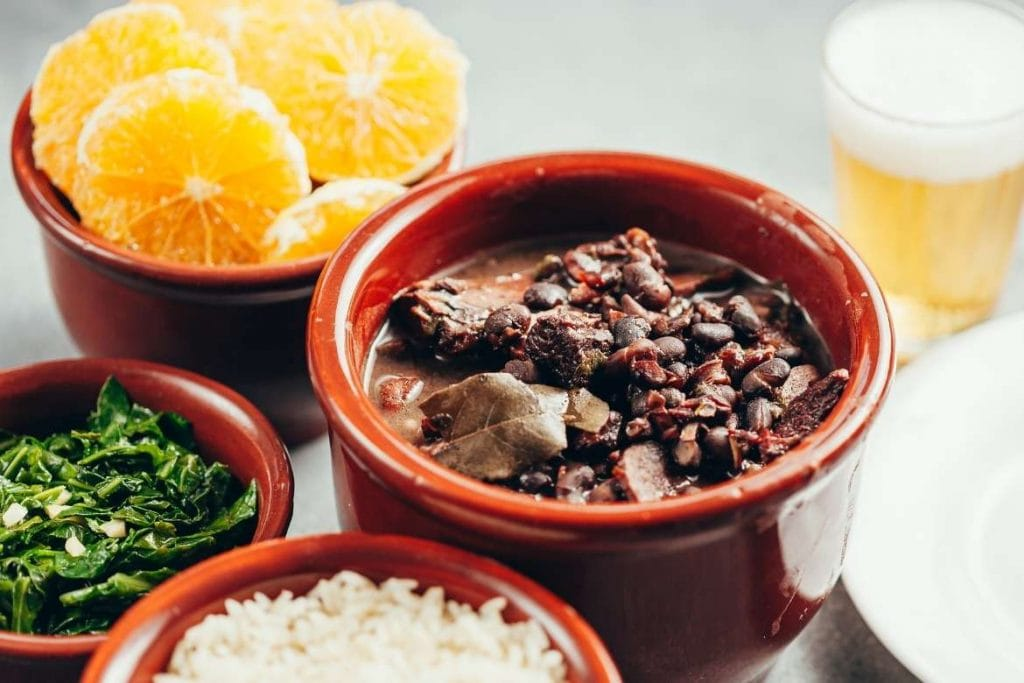 a traditional brazilian feijoada with side dishes including collard greens, rice, pork meat, beans, orange and more
