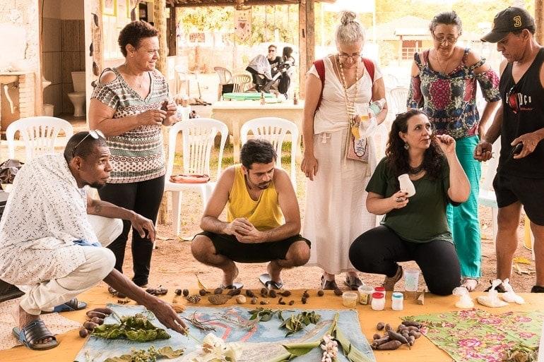 Pessoas cheirando e provando as diferentes plantas do bioma cerrado na oficina sabor do cerrado durante o festival natureza do sabor