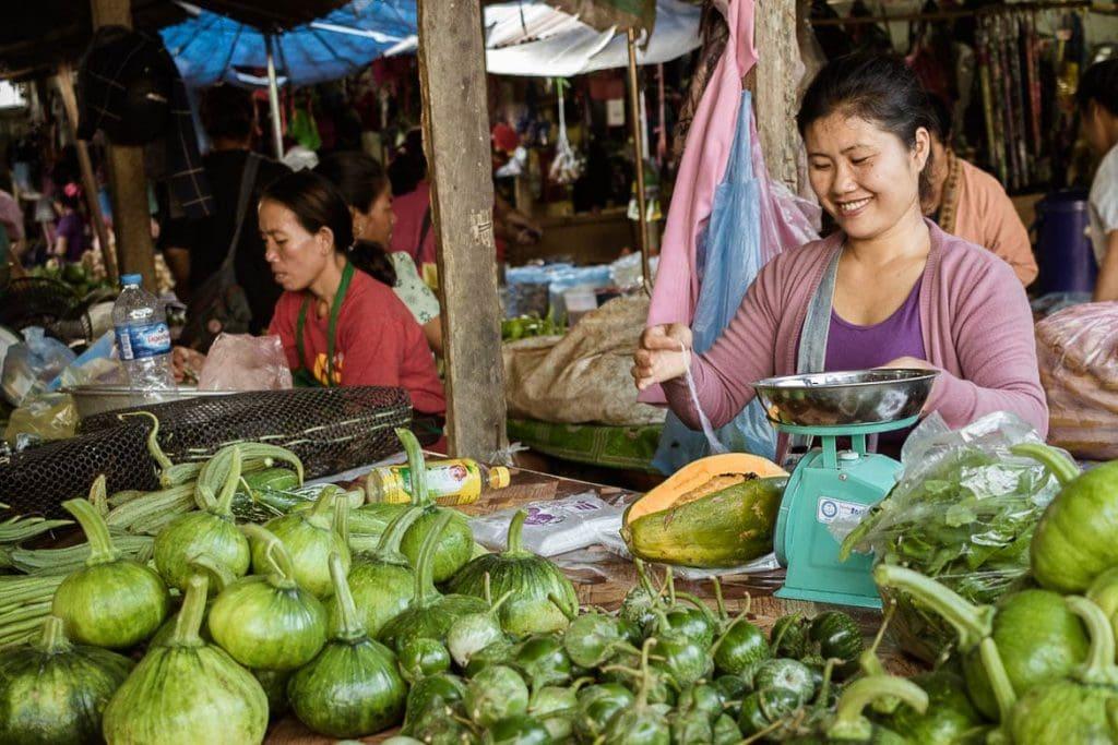 uma barraca de verduras no mercado em Laos durante um tour gastronômico como parte do turismo gastronômico