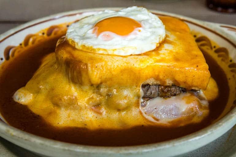 a tradicional francesinha de porto com muito queijo e um ovo estalado por cima