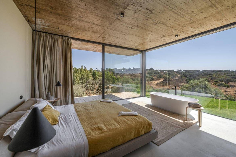 Quarto com paredes de vidro com vista panorâmica para as vinhas da Herdade Malhadinha Wine Hotel - uma das melhores vinícolas com hotel em Portugal