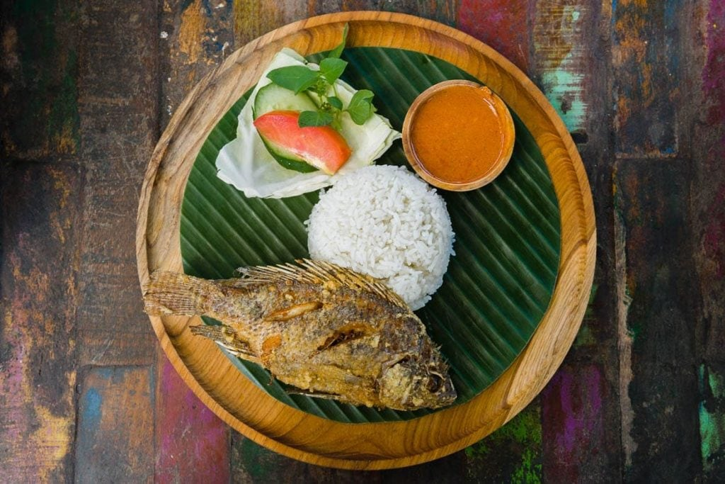 prato na folha de banana com peixe frito, arroz e molho de pimenta sambal prato típico da Indonésia