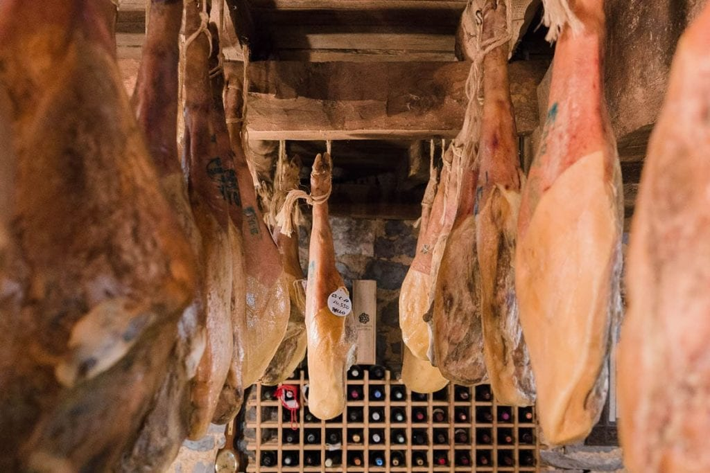 curated spanish jamon iberico hanging on a cellar walls