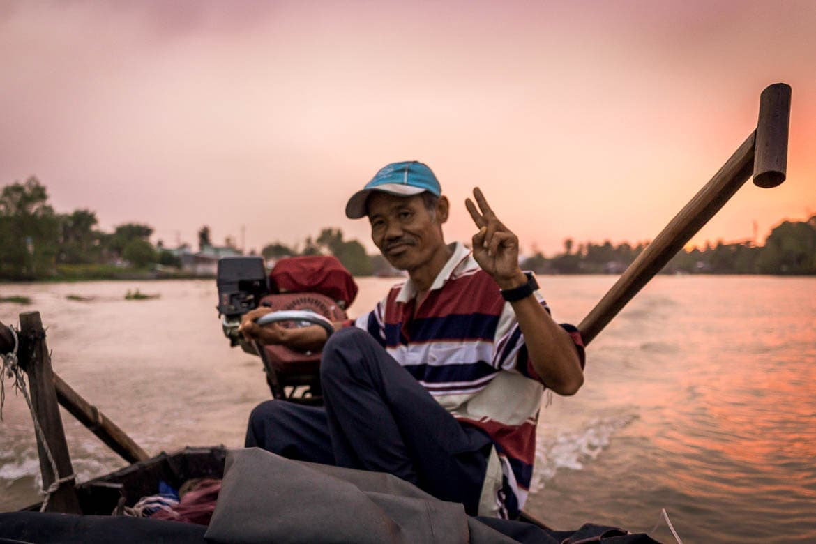 local host driving a boat on the Mekong river during a community based tourism in Vietnam