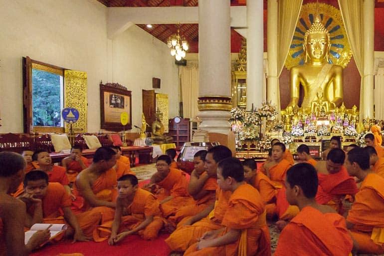 monges estudando o budismo theravada no templo