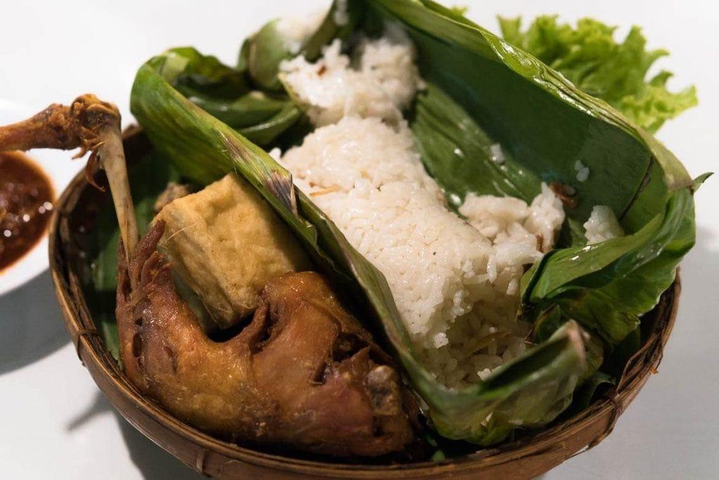 arroz cozido no vapor e depois grelhado na folha de bananeira servido com frango frito e tofu tradicional da Indonésia