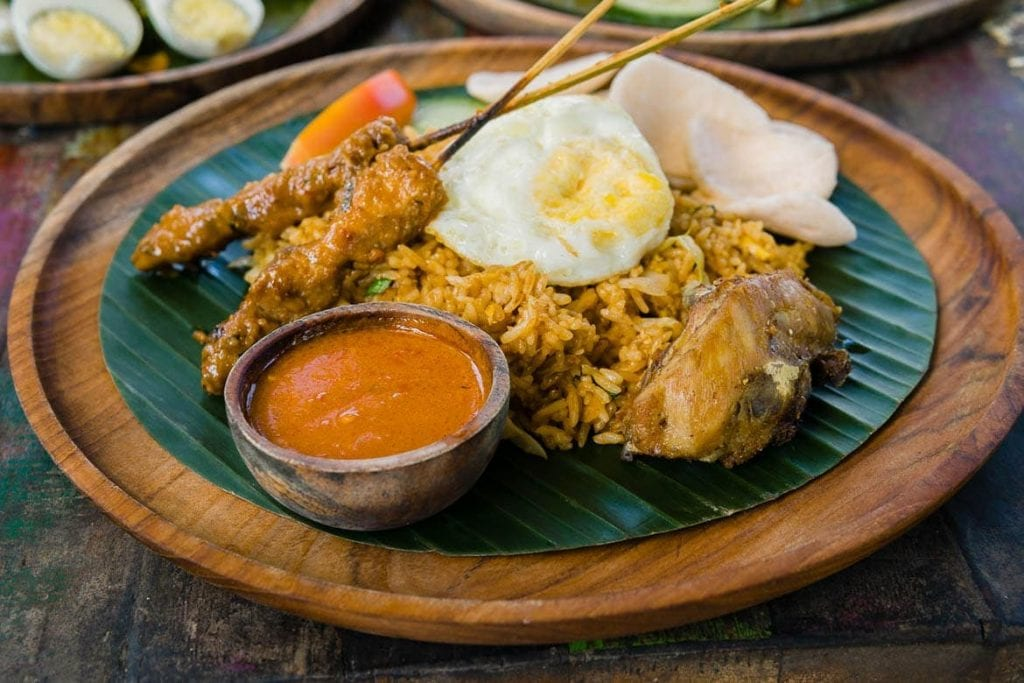 nasi campur na folha de bananeira é um dos pratos mais típicos da Indonésia feito com satay, ovo, arroz, frango e sambal