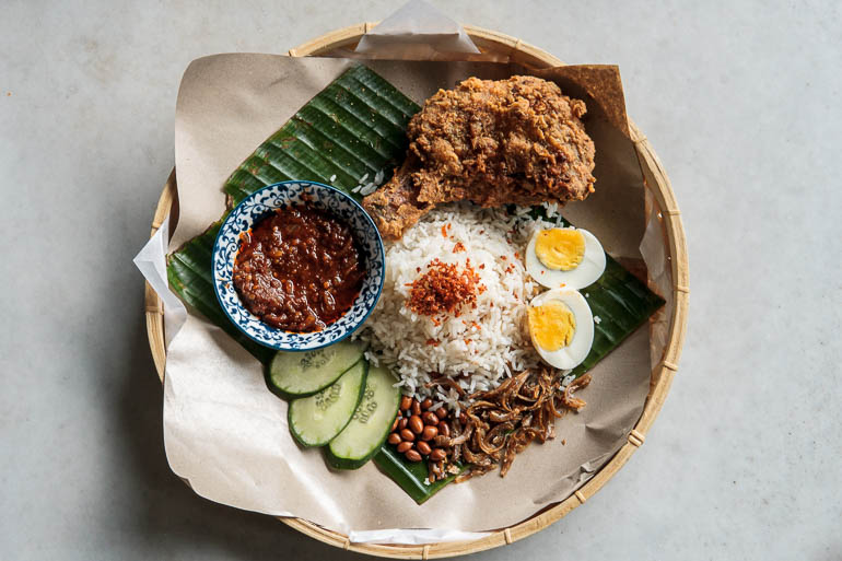 Nasi Lemak, typical malaysian food national dish with rice, eggs, sambal, anchovies and fried chicken