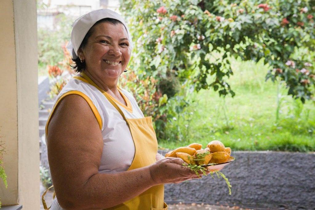 Dona Nilda segurando um prato com pastel de angú de Itabirito