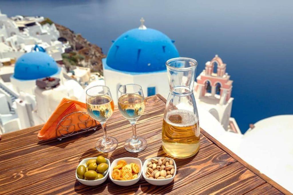 vista para o mar e uma mesa com vinho branco em Santorini, Grécia