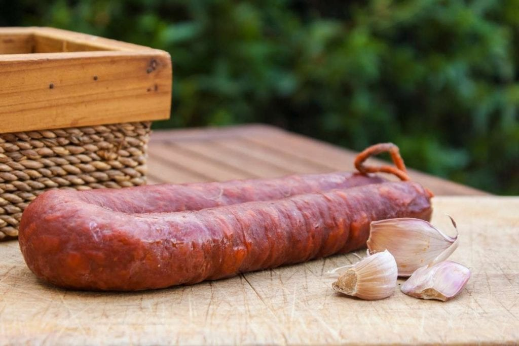 spanish chorizo on a wooden table with garlic