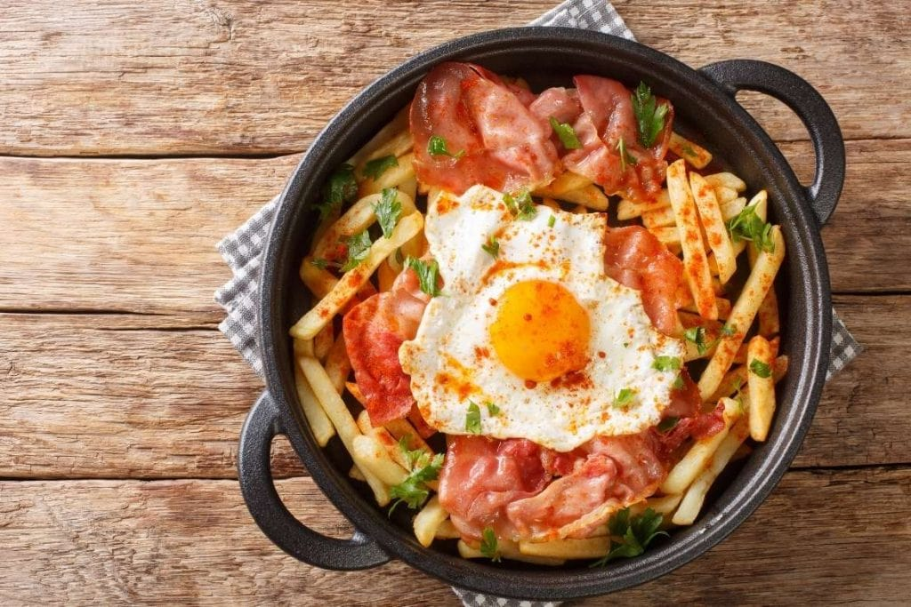 huevos rotos with fried potatoes cured ham and fried eggs on top typical spanish food and tapas