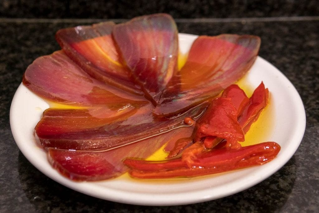 thin slices of mojama with olive oil serve on a plate a very popular food in Spain