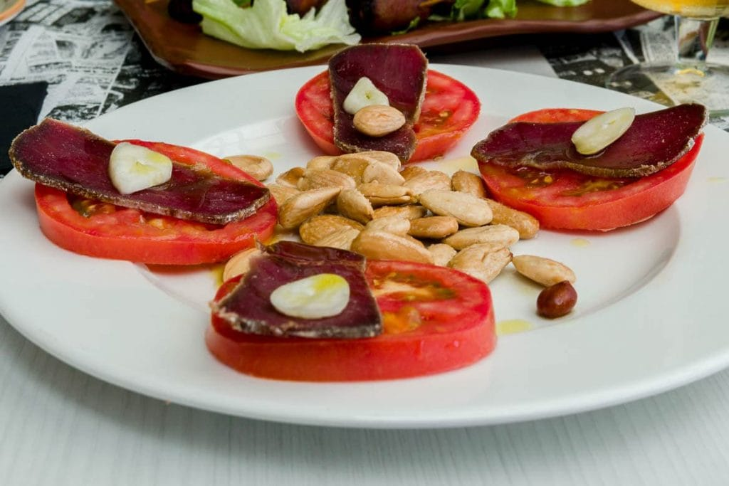 mojama on top of tomato slices and peanuts served as a traditional spanish food