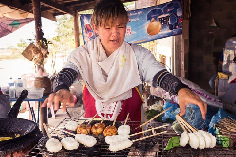 Street vendor of sticky rice grilled in a skewer in Laos