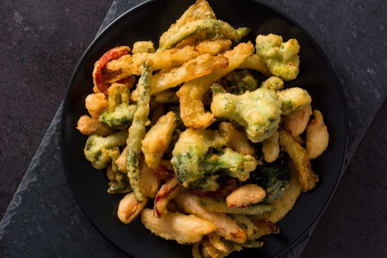 A bowl with vegetable tempura is a traditional snack from Portugal and popularized by Japan