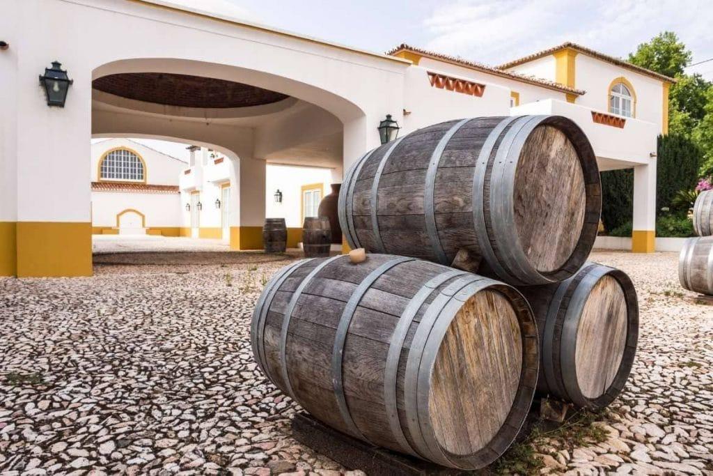 Vinícola portuguesa com paredes brancas e amarelas e barricas de vinho em frente para decoração para receber turistas no Alentejo