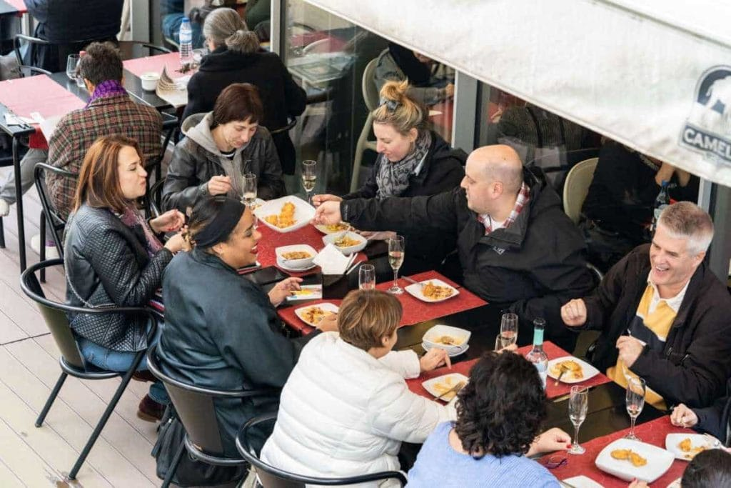 a group of travelers sitting on a table and enjoying Portuguese food in Lisbon