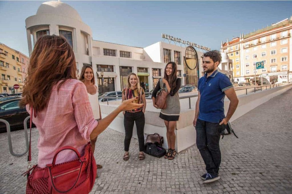 a food tour guide explaining about Lisbon to a group of travellers during a food and culture walking tour